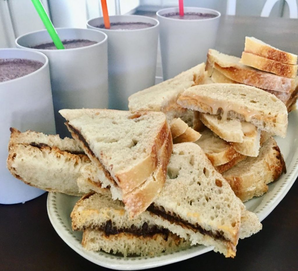 plate of sourdough bread sandwiches and smoothies on the side