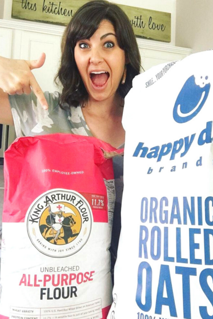 woman showing off bulk foods like 25 pound bag oats