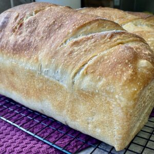 freshly baked sourdough bread sitting on a cooling rack