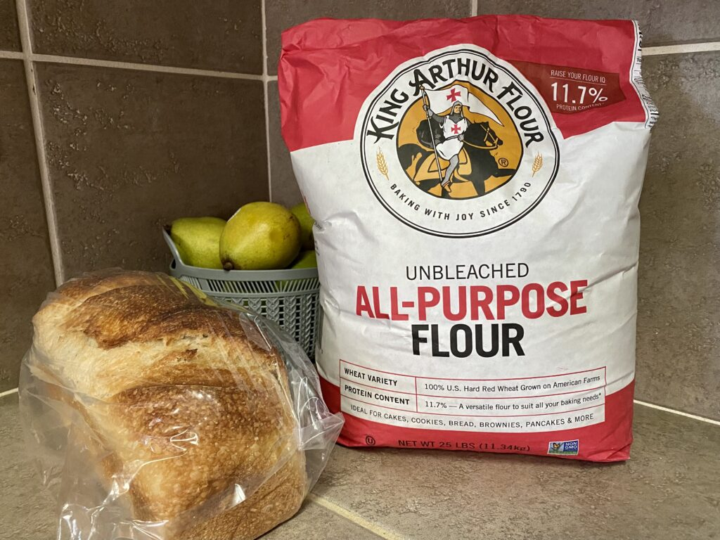 25 pound bag of King Arthur flour and a loaf of sourdough bread