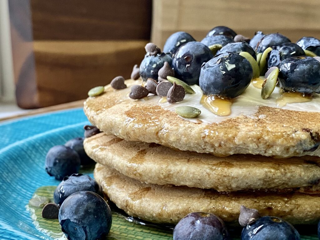 blue plate of 3 oatmeal pancakes topped with blueberries and chocolate chips