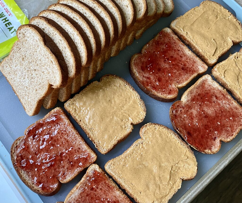 cutting board with a loaf of bread making peanut butter and jelly sandwiches