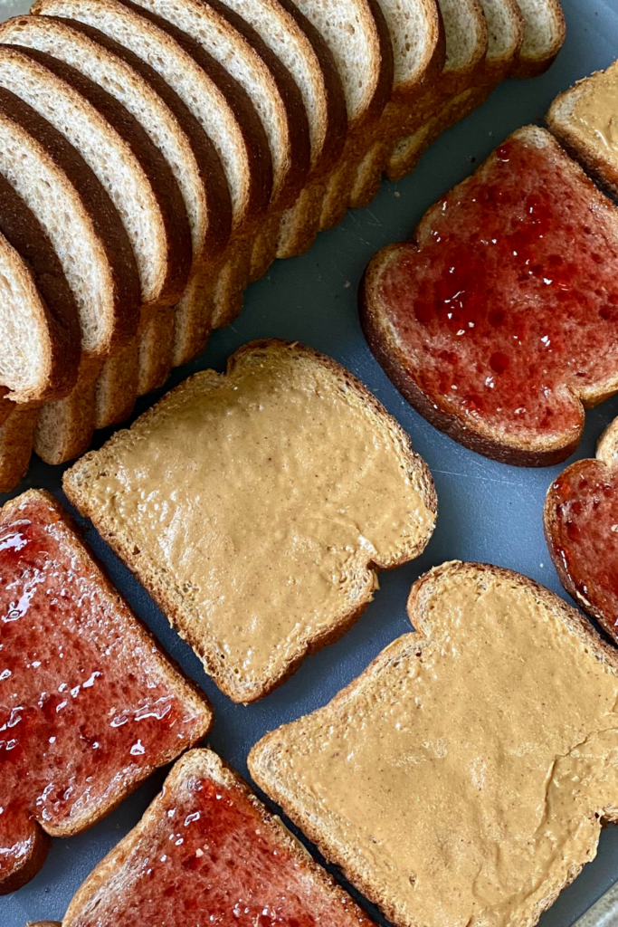 cutting board filled with pieces of bread making peanut butter and jelly