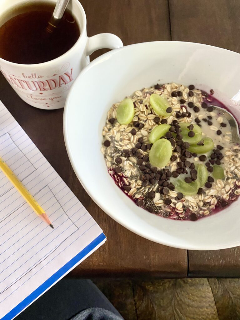bowl of raw oatmeal topped with grapes