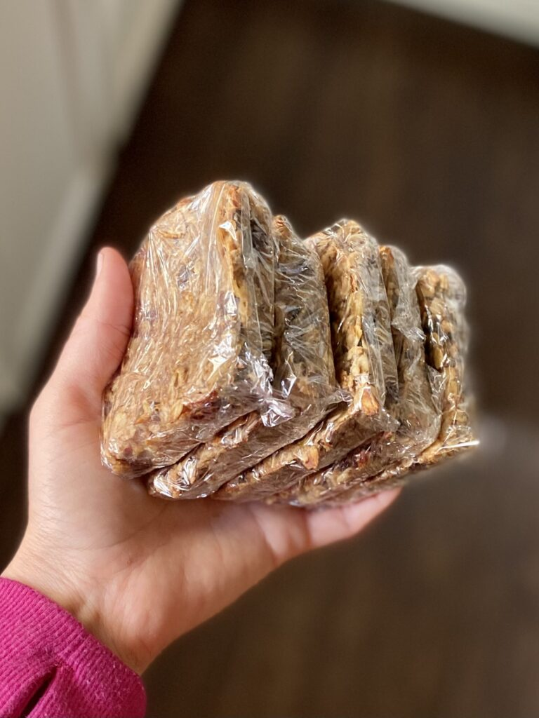 holding breakfast bars wrapped in pastic wrap