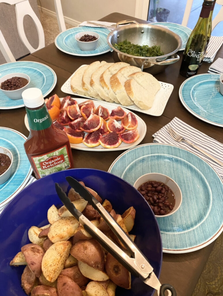 dinner table set with sliced oranges, steamed kale, sourdough bread, roasted potatoes, and black beans