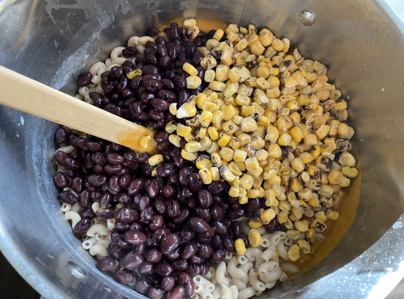 adding black beans and fire roasted corn to chili queso mac