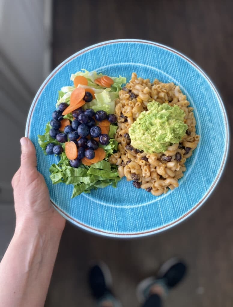 blue plate filled with salad and chili queso mac