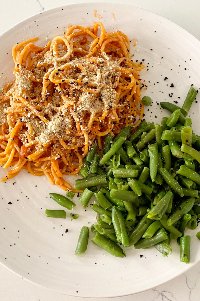 white plate of spaghetti and green beans cheap food