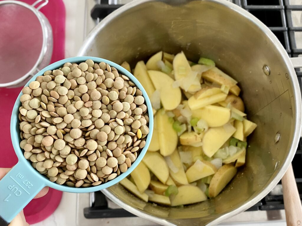 1 cup lentils being added to zuppa toscana soup cozy lentil soup for fall.
